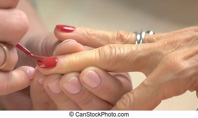 The manicurist paints the nails of woman. Manicure in...