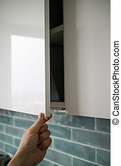 the man's hand is opened by a modern hanging cabinet for a kitchen without door handles