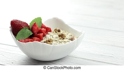 The man's hand puts a plate of muesli on the table. Healthy breakfast. Oatmeal with strawberry and nuts into white bowl
