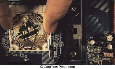 The man's hand puts the bitcoins in a column. Hand counting bitcoins on the motherboard. Crypto currency Gold Bitcoin - BTC - Bit Coin.