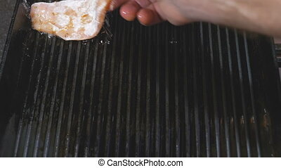 The man's hand, puts the turkey fillet on a hot frying pan - grill. Prepares homemade chops. Delicious.