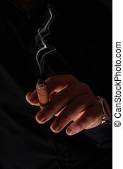 The man's hand with hours, holds a smoking cigar