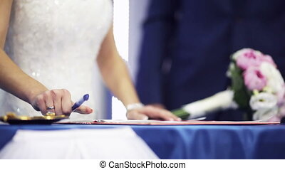 The marriage contract - Newlyweds by turns sign a marriage...