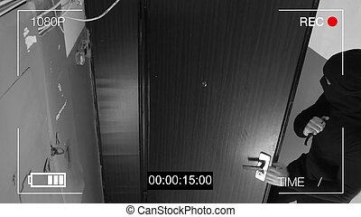 the masked robber c with a knife broke into the apartment. CCTV camera