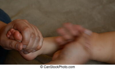 The massage therapist does for the one year old baby boy child rehabilitation massage.