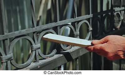 the master cleans the metal fence from rust