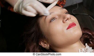 The master hands wipe the client eyebrows with antiseptic before the procedure permanent makeup correction of the shape of the eyebrows to a young beautiful girl. Microblading, eyebrow tattoo.
