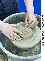 The master teaches the child, a student of pottery. Helps to make out of clay on a Potter's wheel a small jug.