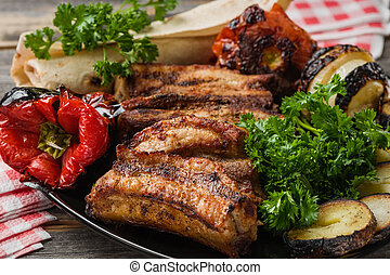 The meat and vegetables roasted on a grill with fresh greens...