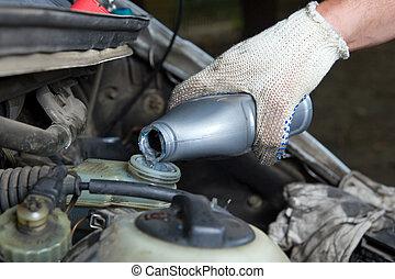 The mechanic fills in a brake liquid
