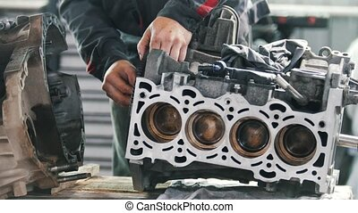 The mechanic lubricates the gear of the valve block of the car engine and repairs it