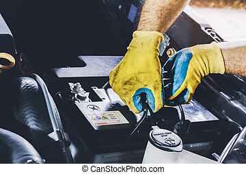 The mechanic pulled the old car battery out of the engine compartment to replace it with a new one in he repair garage