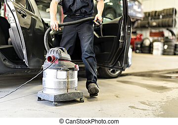 mechanic vacuuming the car at the garage