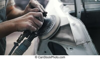 The mechanic's hands grind the car body with a grinder....