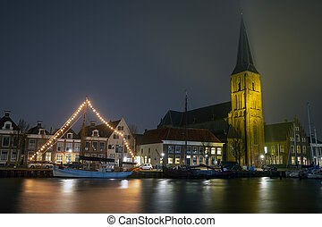 The medieval church with decorated sailing ship in Harlingen in the Netherlands at night