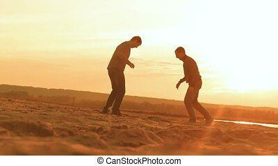 the men on the beach laughing and kicking a ball chase slow...