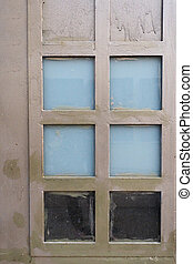 The metal door, painted in a dirty beige color with squares of windows, a part of the windows is milky blue glass.