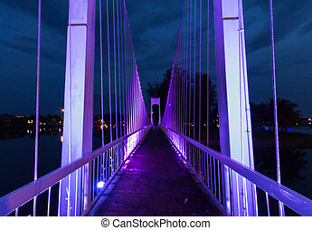 The metal rope bridge in the park at twilight time