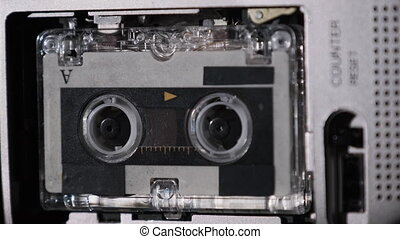 The microcassette spins in a portable handheld recorder. Close-up. Portable Tape player Records Sound or Interviews on a Mini Cassette. Rec of voice on retro recorder. Vintage player. Macro. 4K 10 bit