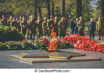 The military salutes monument to soldiers who died in World War. Victory Day Parade. Eternal Flame monument with star and flowers at Grave of Unknown Soldier - symbol of victory in Second World War