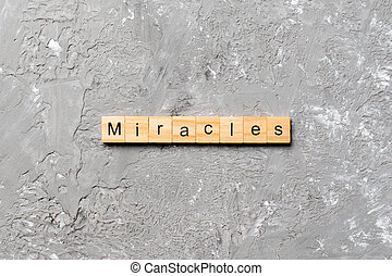 miracles word written on wood block. miracles text on cement table for your desing, concept