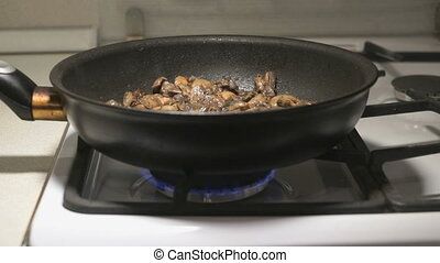 The mix of mushrooms is fried in a black pan