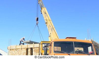 The mobile crane drops the concrete slab on the building....
