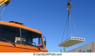 The mobile crane lifts the concrete slab into the air - The...