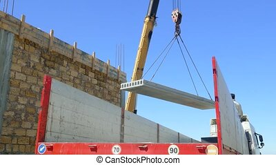 The mobile crane lifts the concrete slab next to the...