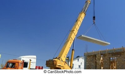 The mobile crane moves the concrete slab to the building. -...