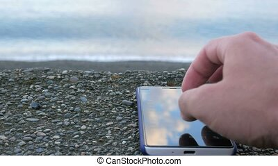 The mobile phone is about the pebble beach of the ocean. Man looking for your photos. Close-up.