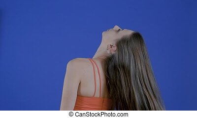 The model shows long hair in the studio on a blue background. Slow motion.