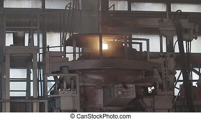 The molten metal is poured. Modern induction furnace in Pouring Hot Liquid Metal From Furnace Metallurgical Plant. Steel industry