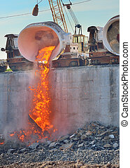 The molten slag is poured from a cup on a railway platform -...