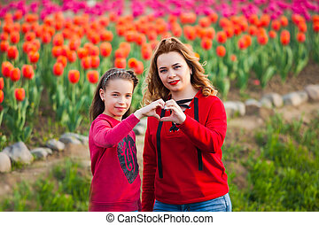 the mom with daughter among a field of wonderful tulips