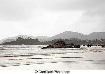 The monsoon change much the landscape of Patnem beach in Goa. India. A sky full of clouds, a gray day and its reflection in the wet sand