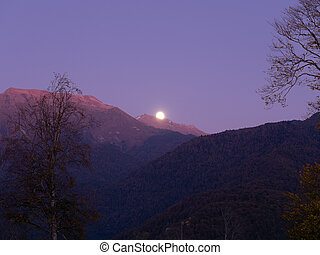 The moon appeared beyond the mountain peaks in the blue sky