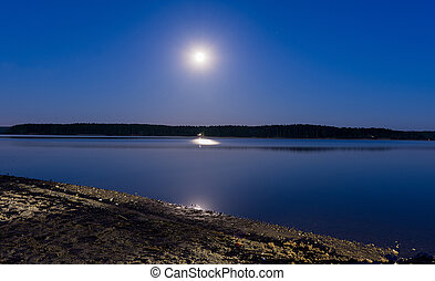 the moon hangs over the lake