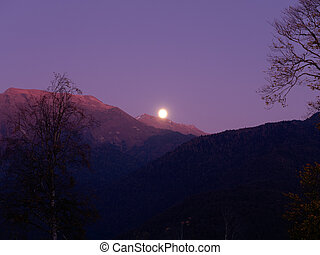 The moon rises over a mountain valley in the blue sky