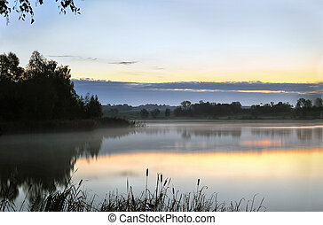 The morning landscape with sunrise over water in the fog