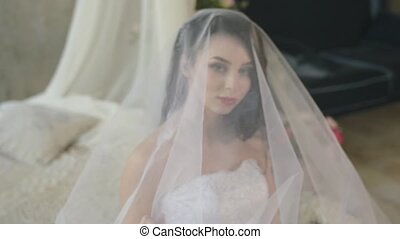 The morning of a gentle attractive brunette. Beautiful bride is smiling and looking out the window touching the veil while sitting on the bed.