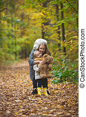 The mother, her daughter and toy Teddy bear posing  walking in autumn park