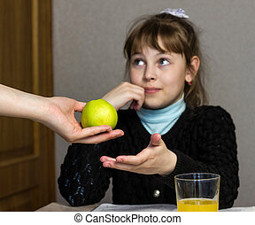 The mother holds out the apple to the girl who goes to school, schoolgirl
