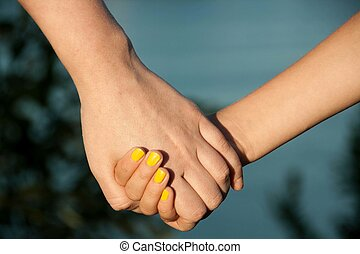 The mother holds the hand of his daughter