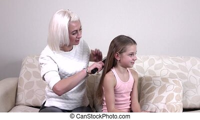 The mother makes her little daughter a beautiful hairstyle