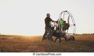 The motor paraglider stands in a field at sunset with a...
