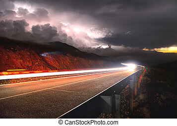 The mountain road with the car passing by the sunset on the right and a thunderstorm with lightning left is shot on a long exposure