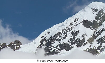 A panning wide shot of the mountain drenched in snow with its peak reaching towards the blue and cloudy sky as the sun shines elegantly through it