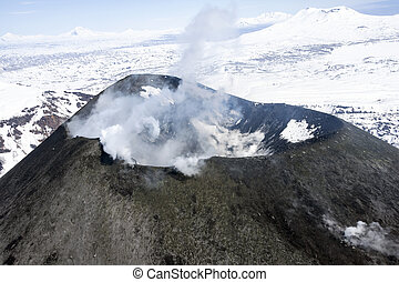 The mouth of an active volcano, with smoke and steam, when ...