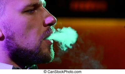 The mouth of man  smoking shisha at restaurant. produces smoke